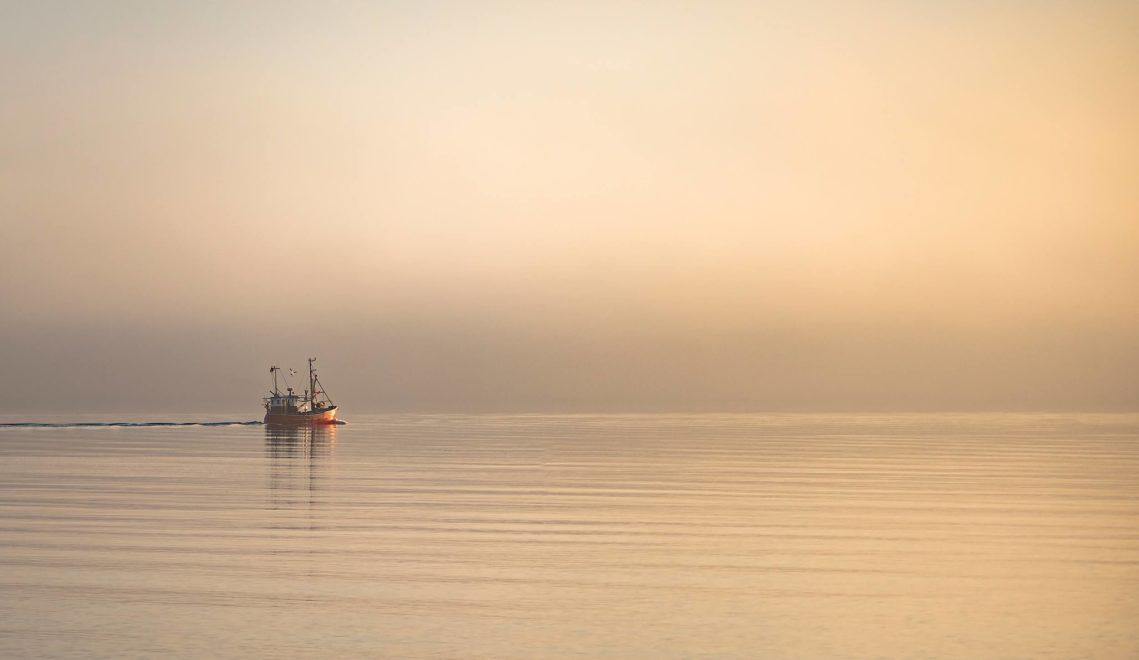 Ostsee-Romantik: Ein Fischerboot fährt am frühen Morgen raus in die Lübecker Bucht © TSNT