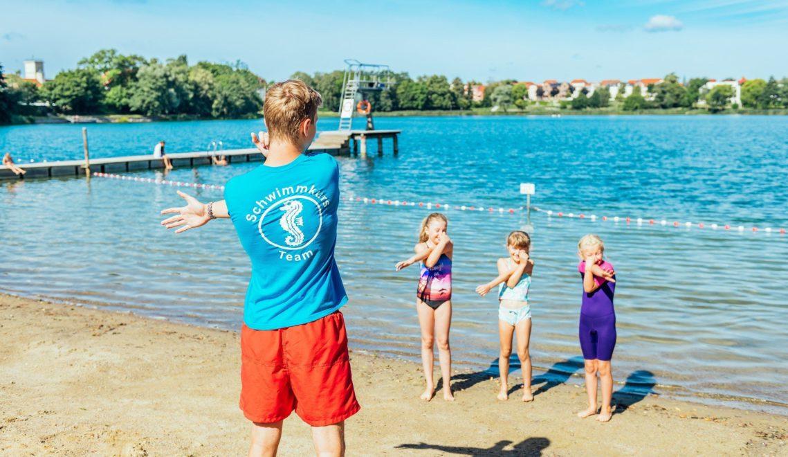 Bevor es ins Wasser geht, zeigt ein Schwimmlehrer den jungen Kursteilnehmern das richtige Dehnen © TMV/Tiemann
