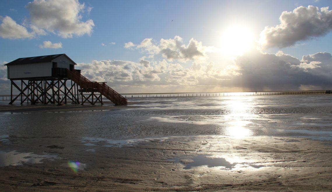 Pfahlbauten aus Lärchenholz ragen seit mehr als einem Jahrhundert am Strand von St. Peter-Ording hervor © TA.SH