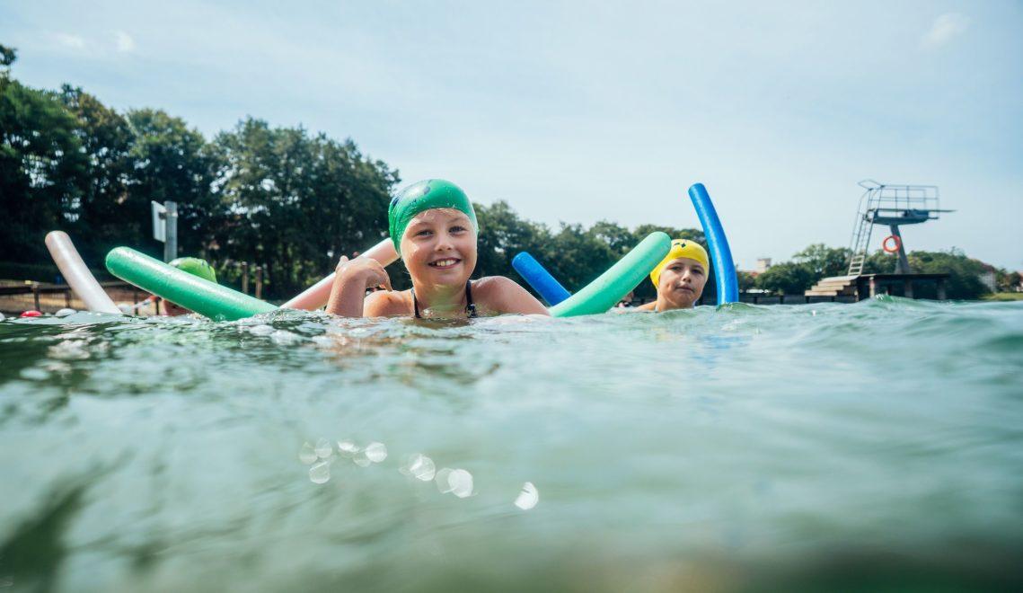 In speziellen Kinderkursen können junge Urlauber das Schwimmen direkt in den Seen lernen © TMV/Gänsicke