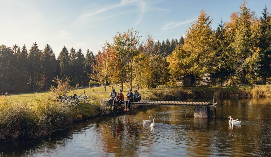 Radfahrer sitzen auf einem Steg am See