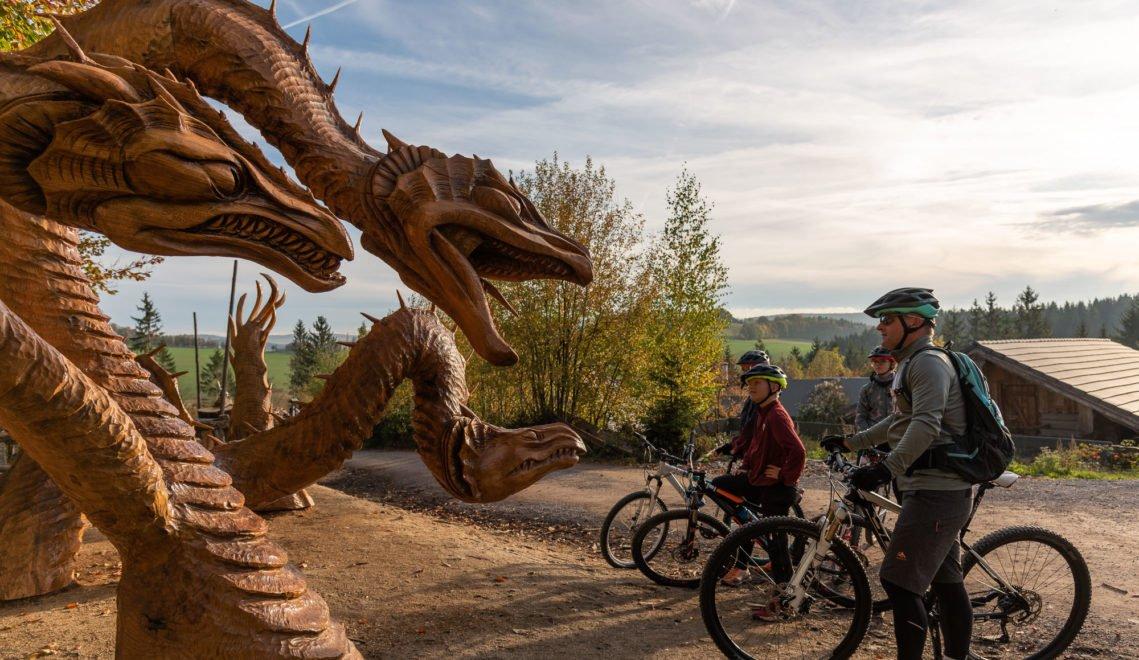 Radfahrer vor Holzdrachen