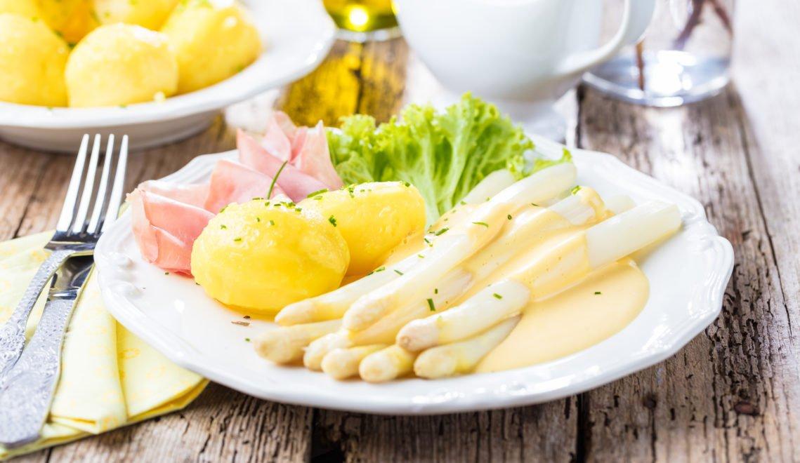 Traditionell wird Spargel mit gerolltem Schinken, Sauce Hollandaise und jungen, in Butter geschwenkten Kartoffeln serviert