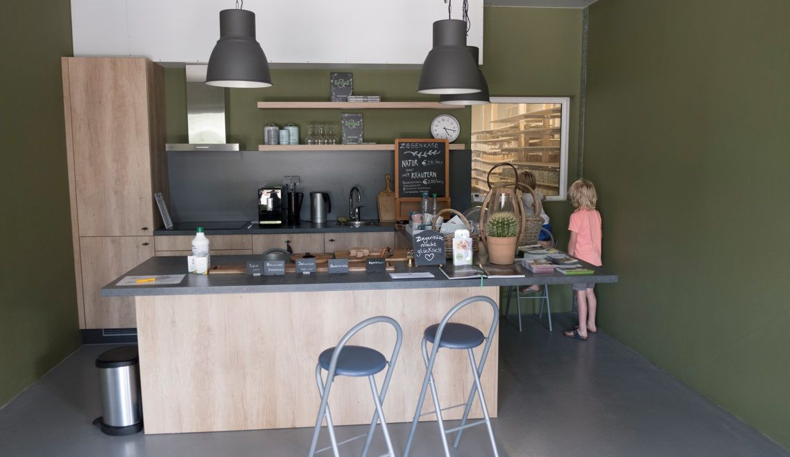 Durch ein Fenster kann man vom modernen Hofladen in die Käserei des Ziegenhofs schauen